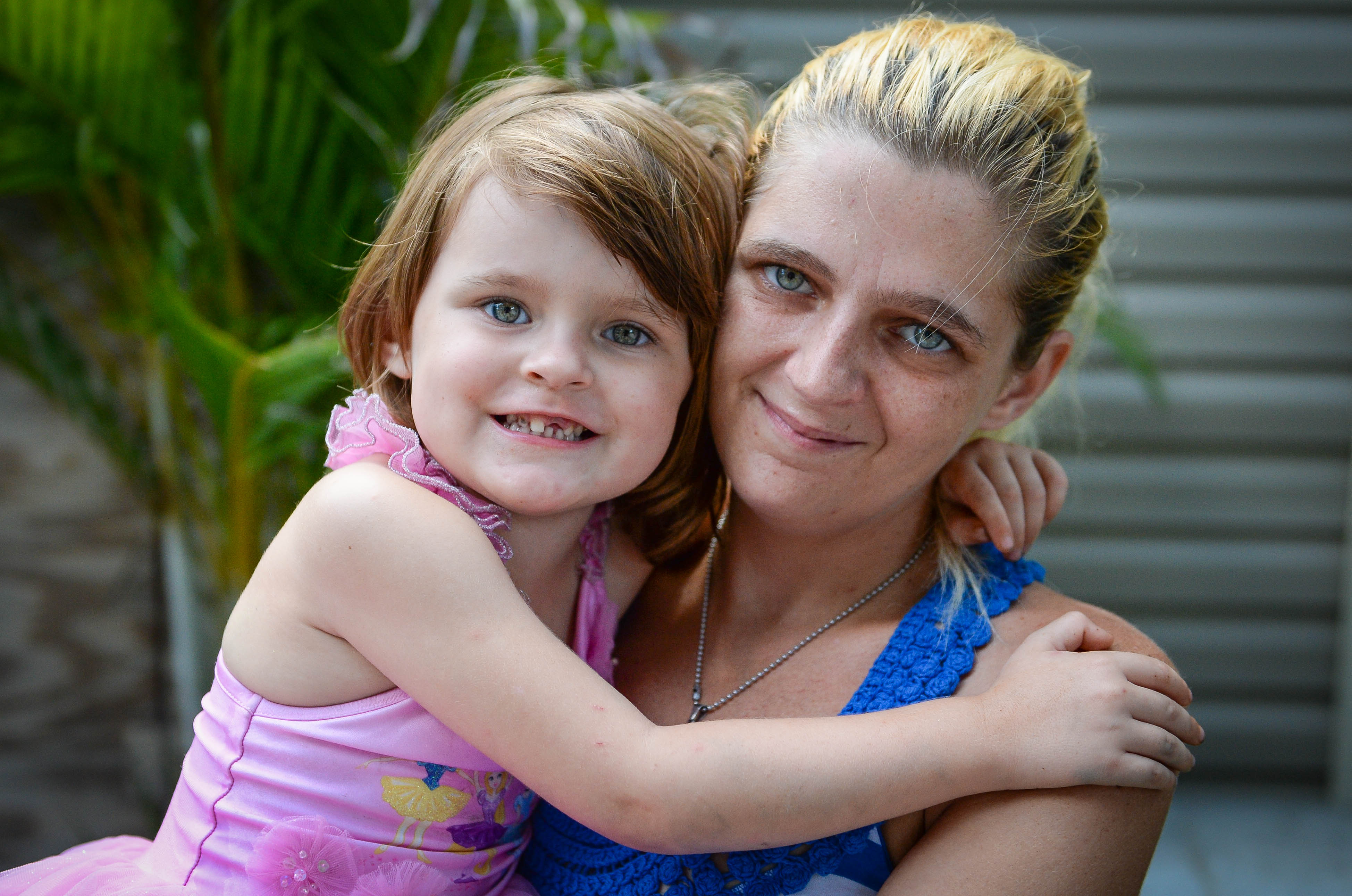 Keriana Carll, 4, and Megan Johnson pose in their yard in Bradenton. Johnson searched for months to find a dentist who was willing to accept Keriana's Medicaid insurance.   STAFF PHOTO / RACHEL S. O'HARA